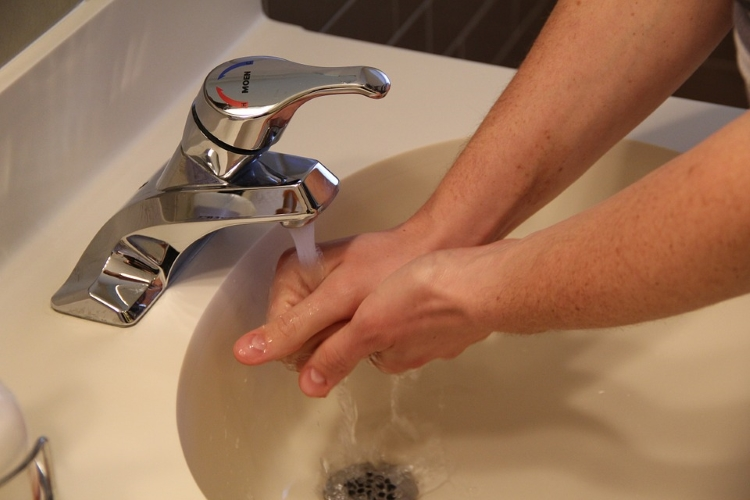 Man Washing Hands Under Running Tap Water