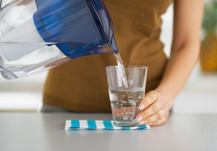 Housewife pouring water into glass from water filter pitcher