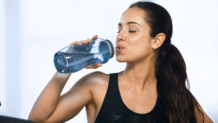Young sportive woman holding water bottle